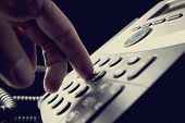 stock photo of keypad  - Person dialing out on a telephone punching in the numbers on the keypad with a finger vintage effect toned image - JPG