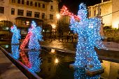 picture of angel-trumpet  - Decorative statues of angels made of lights in a street of the city for Christmas - JPG