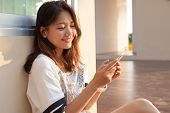 stock photo of sms  - portrait of beautiful young and teen woman looking to mobile phone with smiling face in home outdoor use for chat talking and internet on line connecting technology - JPG