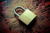 picture of cybercrime  - metal security lock on computer circuit board - JPG