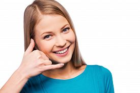 stock photo of gesture  - Cheerful young women gesturing phone sign and smiling while standing against white background - JPG