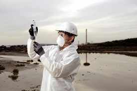 stock photo of water pollution  - Worker in a protective suit examining pollution in the water at the industry. hands holding test tubes for pollution control.