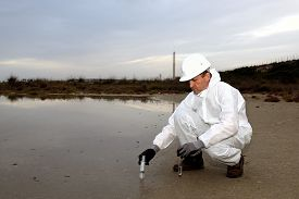picture of groundwater  - Worker in a protective suit examining pollution in the water at the industry - JPG