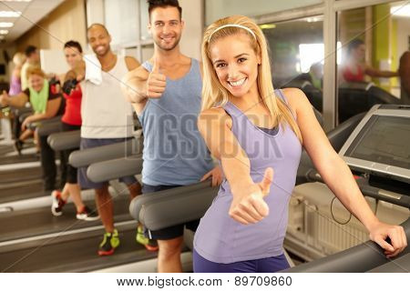 Successful happy people smiling thumbs up in gym.