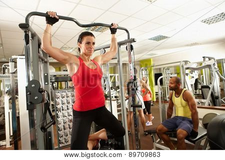 Determined muscular woman doing pull-up workout in gym.