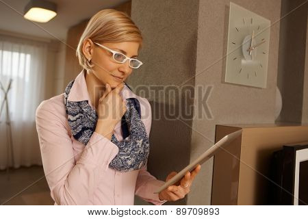 Blonde businesswoman using tablet computer at home, concentrating.