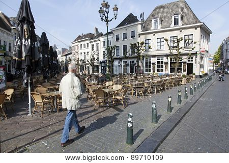 Man Walks along terrace of Havermarkt In Breda