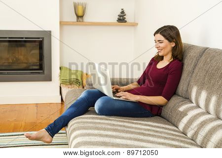 Beautiful woman working from the confort of home with her laptop