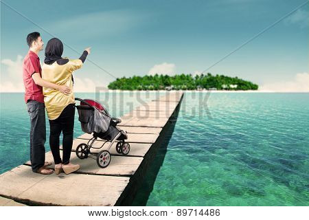 Young Parents On The Pier With A Stroller