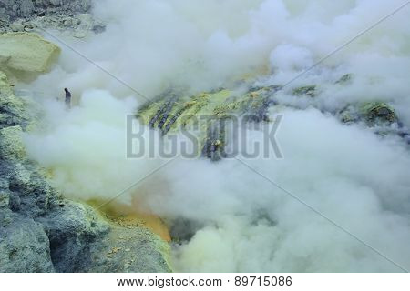 KAWAH IJEN, INDONESIA - AUGUST 8, 2011: Miners collect sulphur in the fumes of toxic volcanic gas at the sulphur mines in the crater of the active volcano of Kawah Ijen, East Java, Indonesia.