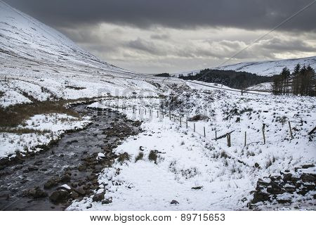 Stream Flowing Through Snow Covered Winter Landscape In Mountain Countryside
