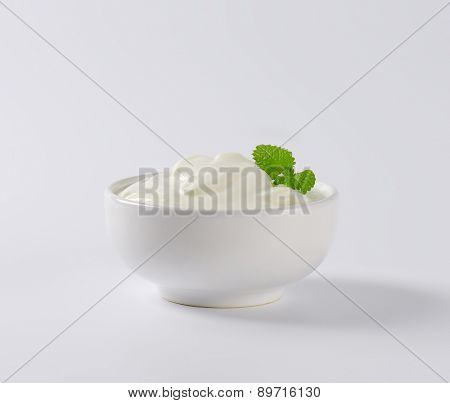 side view of bowl with sour cream on an off-white background with shadows