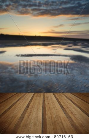 Vibrant Sunrise Landscape Reflected In Low Tide Water On Beach With Wooden Planks Floor