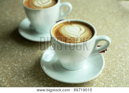 Cups of cappuccino with heart on foam on table in cafe