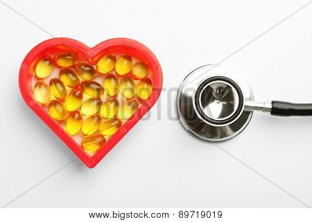 Heart of cod liver oil and stethoscope, isolated on white