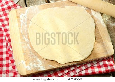 Rolled dough on cutting board with rolling pin on table close up