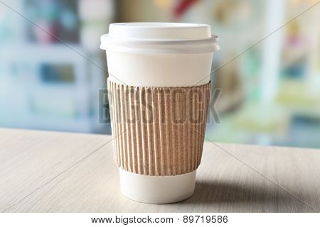 Paper cup of coffee on table on bright background