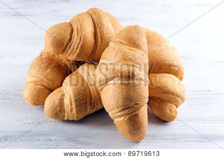 Delicious croissants on table on light background