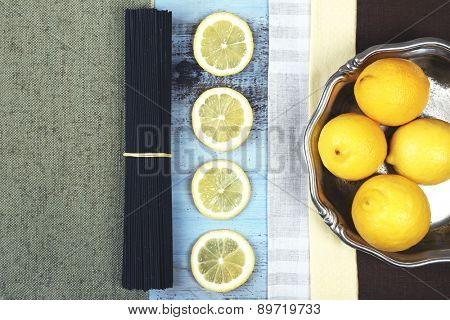 Black spaghetti and lemons on wooden table top view
