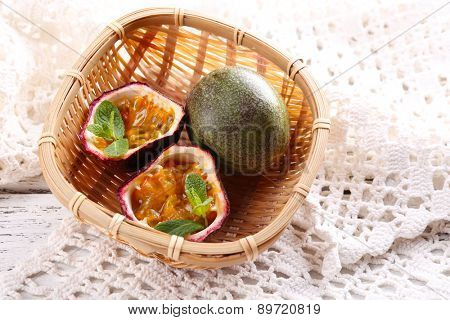 Passion fruits in basket on color wooden background