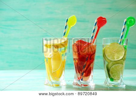 Cocktails with fresh strawberries and lemons on wooden background