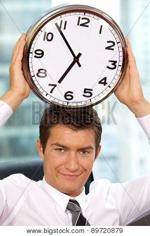 Portrait of smiling businessman holding clock to his head