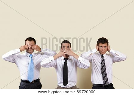 Three businessman covering eyes, mouth and ears