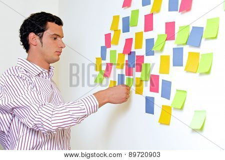 Businessman looking at wall of sticky notes