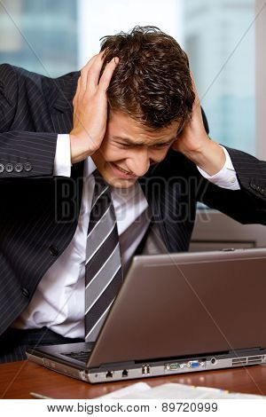 Businessman using laptop with head in hands