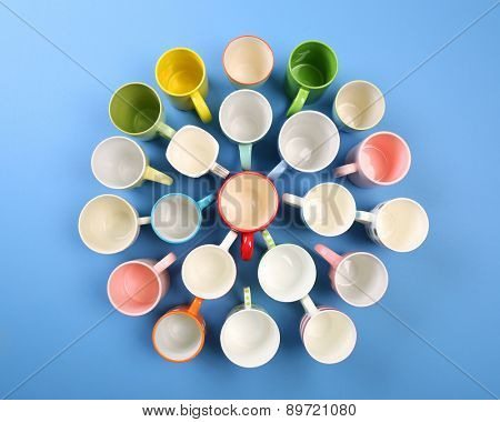 Group of colorful cups on color table, top view
