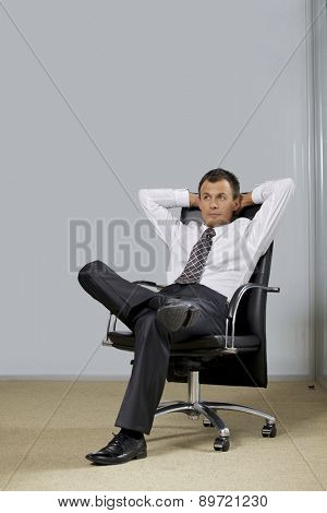 Businessman sitting in office, hands behind head