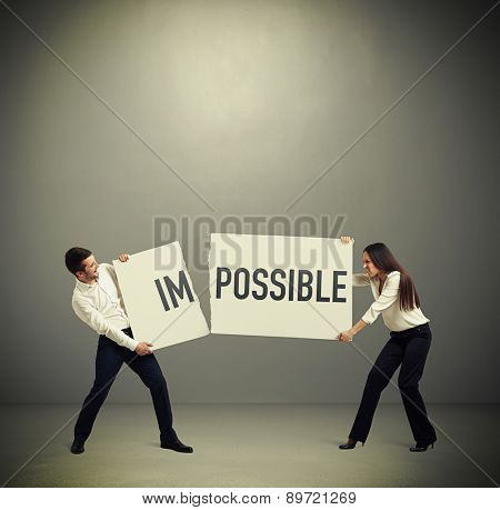 businessman and businesswoman tearing banner with word impossible for possible over dark background
