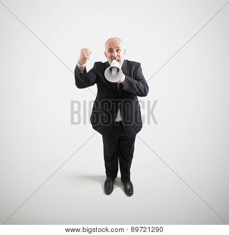top view of angry screaming senior businessman with megaphone showing fist and looking at camera over light grey background