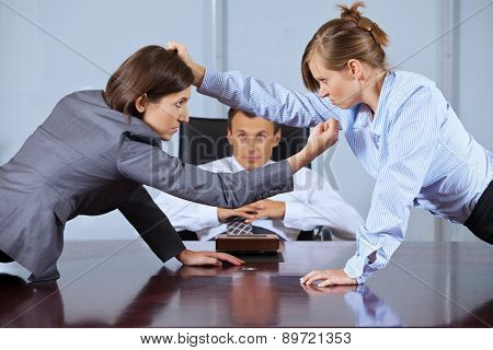 Businesswomen arguing in front of businessman at office