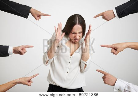 many fingers pointing at stressed businesswoman over light grey background