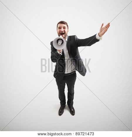 view from above of happy businessman with megaphone over light grey background