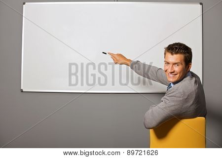 Portrait of businessman pointing at whiteboard in office
