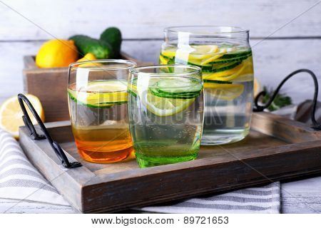 Fresh water with lemon and cucumber in glassware in wooden tray, closeup