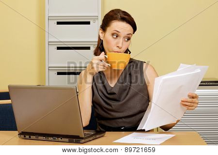 Businesswoman having tea while looking at documents in office