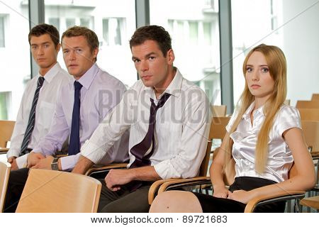 Portrait of business executives sitting in row at office