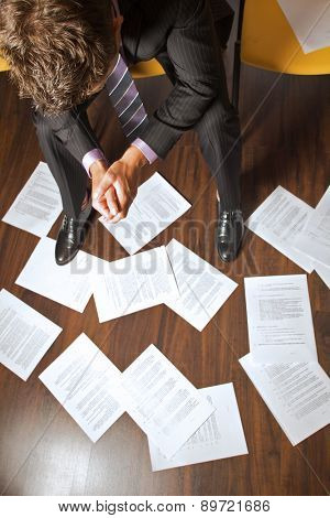 Businessman with clasped hands looking at documents scattered on floor