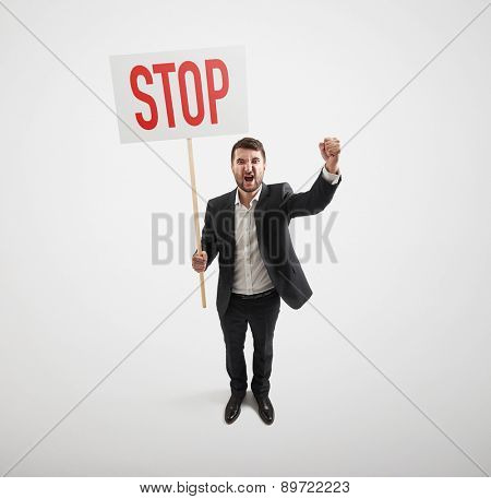 view from above of screaming businessman holding placard with stop sign over light grey background