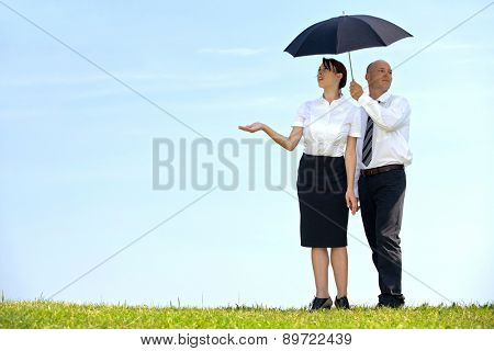 Businessman and businesswoman under umbrella in park