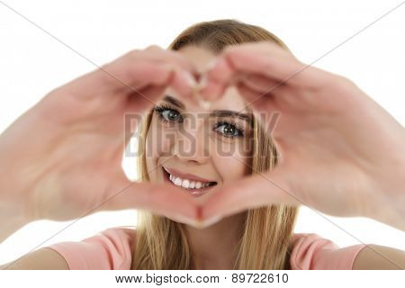 Smiling attractive young woman makes the heart using fingers