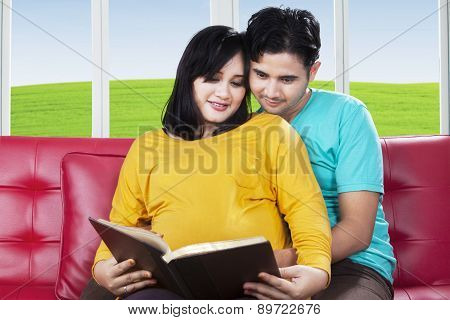 Pregnant Woman Reading Book With Husband