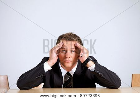 Portrait of businessman sitting with head in hands in office