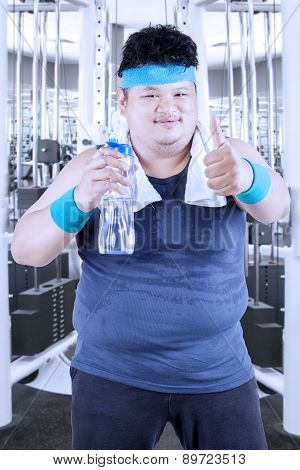 Obese Man Drinks Water At Gym