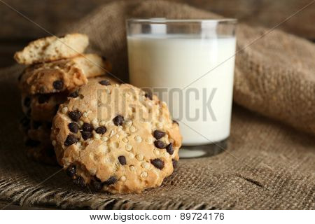 Tasty cookies and glass of milk on rustic wooden background