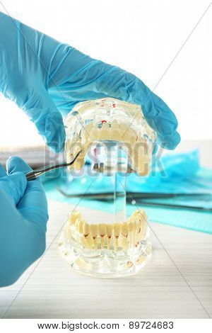 White fake teeth in hand of dentist, on light background