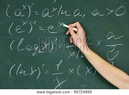 Female hand writing formulas on blackboard with chalk, close up